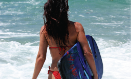 image of girl in bikini walking into the surf